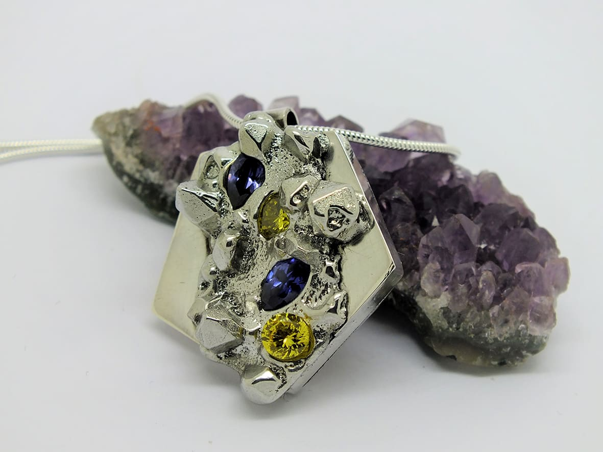 """<span class=""""link fancybox-details-link""""><a href=""""/artists/154-stacey-west/works/3946-stacey-west-found-treasures-pendant-large-2017/"""">View Detail Page</a></span><div class=""""artist""""><strong>Stacey West</strong></div> <div class=""""title""""><em>'Found Treasures' Pendant – large</em>, 2017</div> <div class=""""medium"""">Pewter and silver with purple and yellow cubic zirconia on sterling silver chain</div><div class=""""copyright_line"""">Copyright The Artist</div>"""