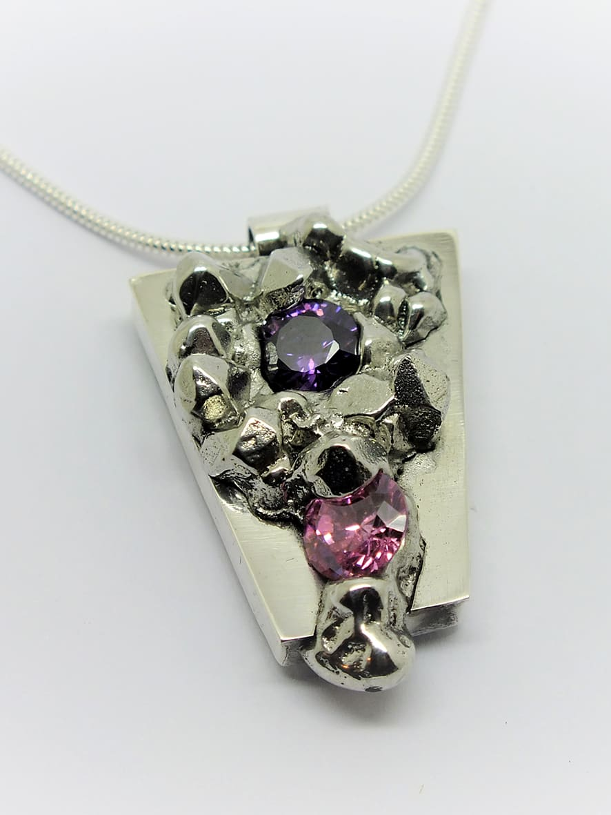 """<span class=""""link fancybox-details-link""""><a href=""""/artists/154-stacey-west/works/3942-stacey-west-found-treasures-pendant-medium-2017/"""">View Detail Page</a></span><div class=""""artist""""><strong>Stacey West</strong></div> <div class=""""title""""><em>'Found Treasures' Pendant – medium</em>, 2017</div> <div class=""""medium"""">Pewter and silver with pink and purple cubic zirconia on sterling silver chain</div><div class=""""copyright_line"""">Copyright The Artist</div>"""