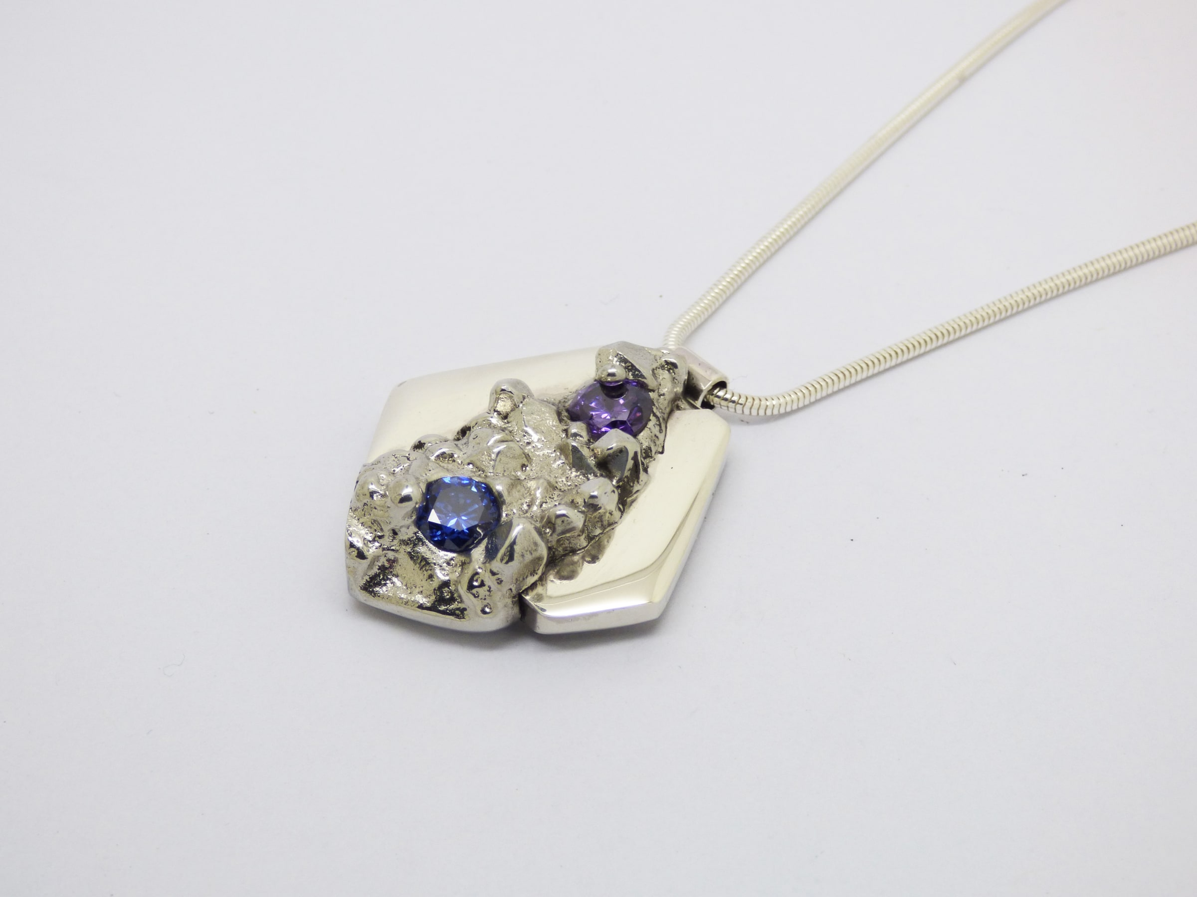 """<span class=""""link fancybox-details-link""""><a href=""""/artists/154-stacey-west/works/4887-stacey-west-found-treasures-pendant-2017/"""">View Detail Page</a></span><div class=""""artist""""><strong>Stacey West</strong></div> <div class=""""title""""><em>'Found Treasures' Pendant </em>, 2017</div> <div class=""""medium"""">Pewter and silver pendant on sterling silver chain with purple cubic zirconia. Large (long chain) 20"""" </div><div class=""""price"""">£155.00</div><div class=""""copyright_line"""">Copyright The Artist</div>"""