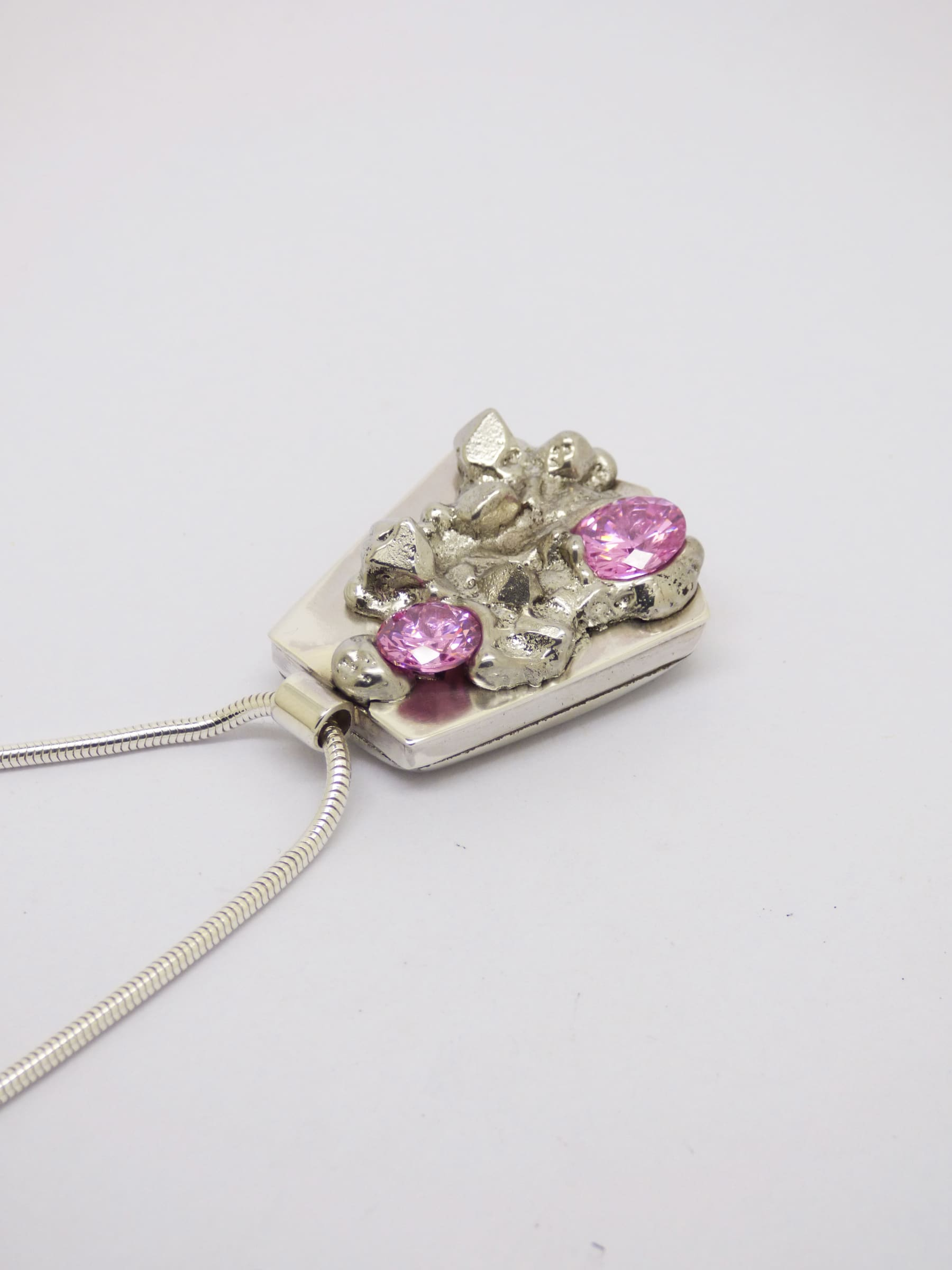 """<span class=""""link fancybox-details-link""""><a href=""""/artists/154-stacey-west/works/4899-stacey-west-found-treasures-pendant-large-2017/"""">View Detail Page</a></span><div class=""""artist""""><strong>Stacey West</strong></div> <div class=""""title""""><em>'Found Treasures' Pendant – large</em>, 2017</div> <div class=""""medium"""">Pewter and silver pendant on sterling silver chain with pink cubic zirconia. -Large (long chain) 20""""</div><div class=""""price"""">£155.00</div><div class=""""copyright_line"""">Copyright The Artist</div>"""