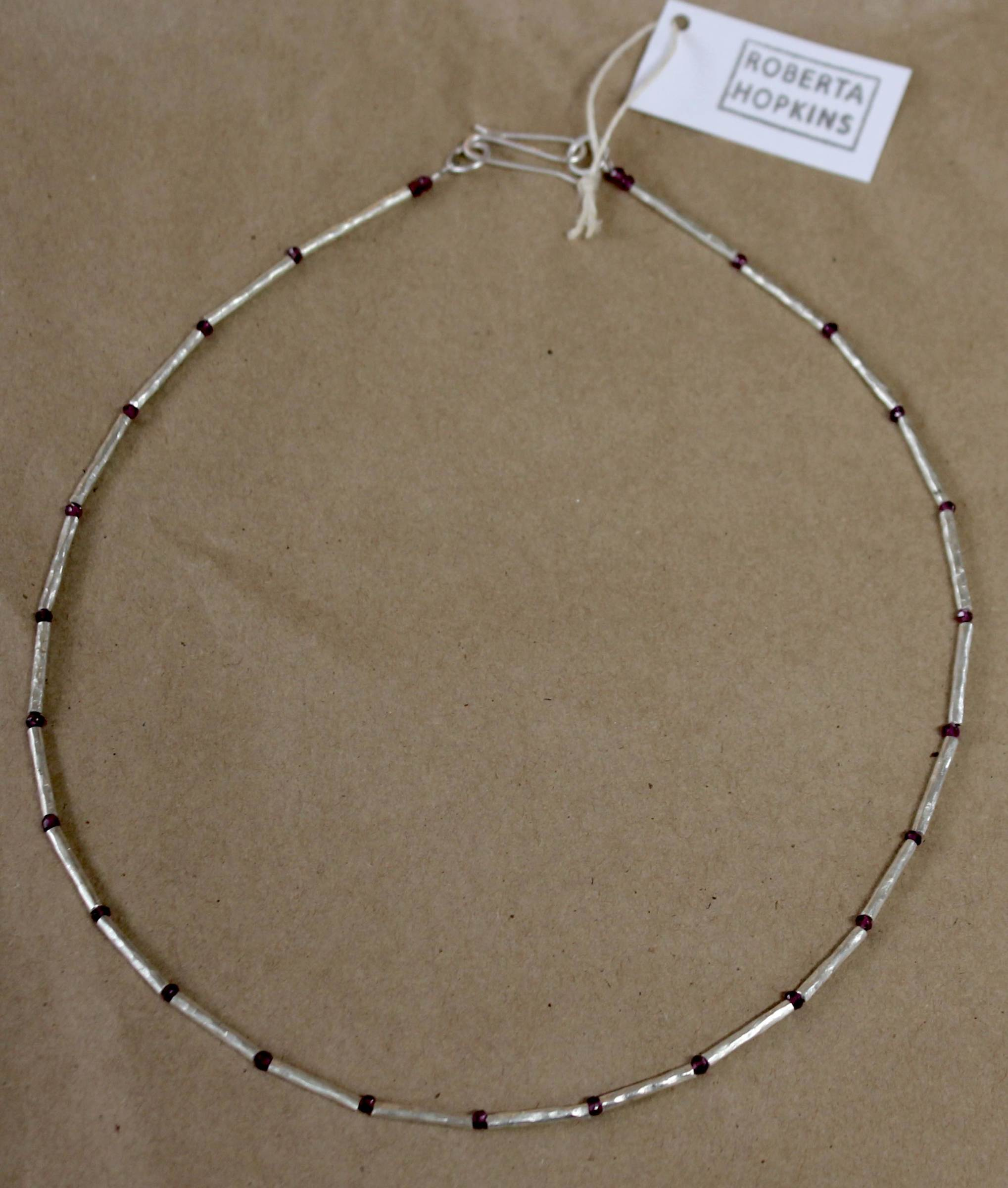 "<span class=""link fancybox-details-link""><a href=""/artists/148-roberta-hopkins/works/5843-roberta-hopkins-faceted-garnets-and-silver-twiggy-tubes-2018/"">View Detail Page</a></span><div class=""artist""><strong>Roberta Hopkins</strong></div> <div class=""title""><em>Faceted Garnets and Silver Twiggy Tubes</em>, 2018</div> <div class=""medium"">sterling silver</div><div class=""copyright_line"">£ 13.50 x 10 Months, OwnArt 0% APR</div>"