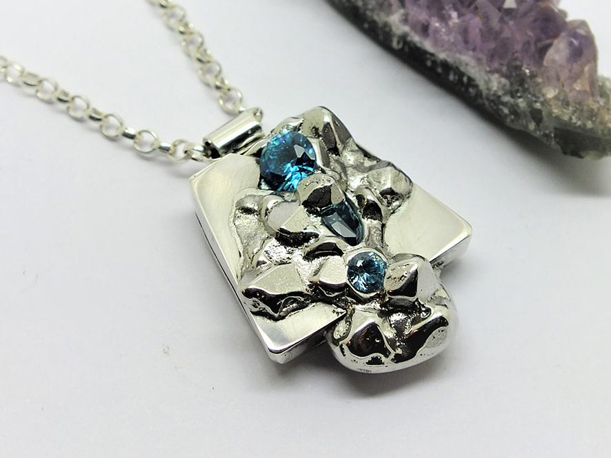 <span class=&#34;link fancybox-details-link&#34;><a href=&#34;/artists/154-stacey-west/works/5093-stacey-west-found-treasures-pendant-large-2017/&#34;>View Detail Page</a></span><div class=&#34;artist&#34;><strong>Stacey West</strong></div> <div class=&#34;title&#34;><em>'Found Treasures' Pendant – large</em>, 2017</div> <div class=&#34;medium&#34;>Pewter and silver with aqua cubic zirconia on sterling silver 18 &#34;chain</div><div class=&#34;price&#34;>£145.00</div><div class=&#34;copyright_line&#34;>Copyright The Artist</div>