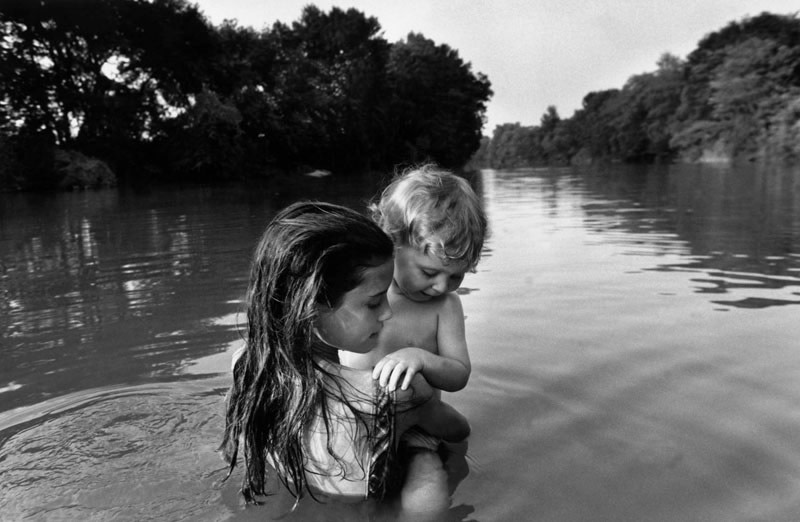 """<span class=""""link fancybox-details-link""""><a href=""""/artists/110/series/the-world-from-my-front-porch/14256-larry-towell-isaac-s-first-swim-lambton-county-ontario-canada-1996/"""">View Detail Page</a></span><div class=""""artist""""><strong>Larry Towell</strong></div> b. 1953 <div class=""""title""""><em>Isaac's First Swim, Lambton County, Ontario, Canada</em>, 1996</div> <div class=""""signed_and_dated"""">Signed, titled, and dated, in pencil, au verso<br /> Printed in 2005</div> <div class=""""medium"""">Gelatin silver print</div> <div class=""""dimensions"""">11 x 14 inch (27.94 x 35.56 cm)</div> <div class=""""edition_details""""></div><div class=""""copyright_line"""">© Larry Towell / Magnum Photos</div>"""