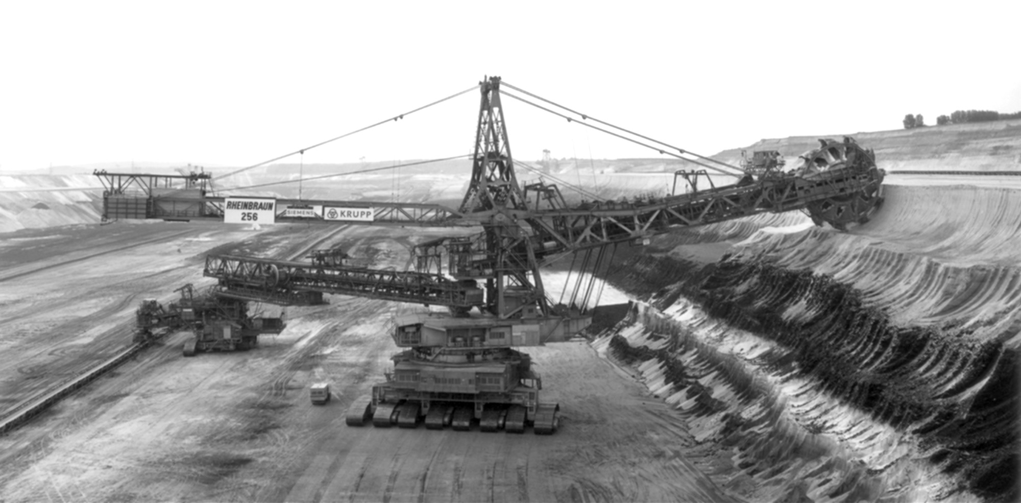 "<span class=""link fancybox-details-link""><a href=""/artists/128-claudia-fahrenkemper/works/35246-claudia-fahrenkemper-shovel-wheel-excavator-256-lignite-mine-garzweiler-germany-1991/"">View Detail Page</a></span><div class=""artist""><strong>Claudia Fährenkemper</strong></div> b. 1959 <div class=""title""><em>Shovel Wheel Excavator 256, Lignite Mine, Garzweiler, Germany</em>, 1991</div> <div class=""signed_and_dated"">From the series ""Mining Machinery""<br /> Signed, titled, dated, and editioned, in pencil, au verso<br /> Printed in 2019</div> <div class=""medium"">Gelatin silver print</div> <div class=""dimensions"">10 ½ x 19 ¾ inch (26.67 x 50.17 cm)</div> <div class=""edition_details"">Edition of 8 + 3 APs (#5/8)</div>"