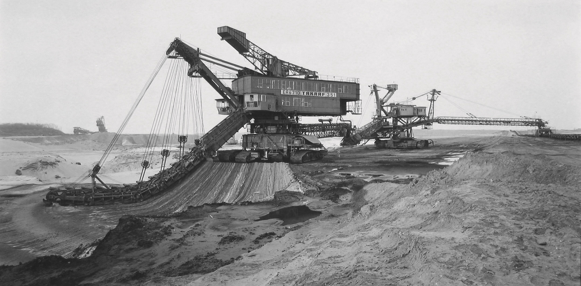 "<span class=""link fancybox-details-link""><a href=""/artists/128-claudia-fahrenkemper/works/35247-claudia-fahrenkemper-bucket-chain-excavator-lignite-mine-profen-germany-1993/"">View Detail Page</a></span><div class=""artist""><strong>Claudia Fährenkemper</strong></div> b. 1959 <div class=""title""><em>Bucket Chain Excavator, Lignite Mine, Profen, Germany</em>, 1993</div> <div class=""signed_and_dated"">From the series ""Mining Machinery""<br /> Signed, titled, dated, and editioned, in pencil, au verso<br /> Printed in 2019</div> <div class=""medium"">Gelatin silver print</div> <div class=""dimensions"">10 ½ x 19 ¾ inch (26.67 x 50.17 cm)</div> <div class=""edition_details"">Edition of 8 + 3 APs (#1/8)</div>"