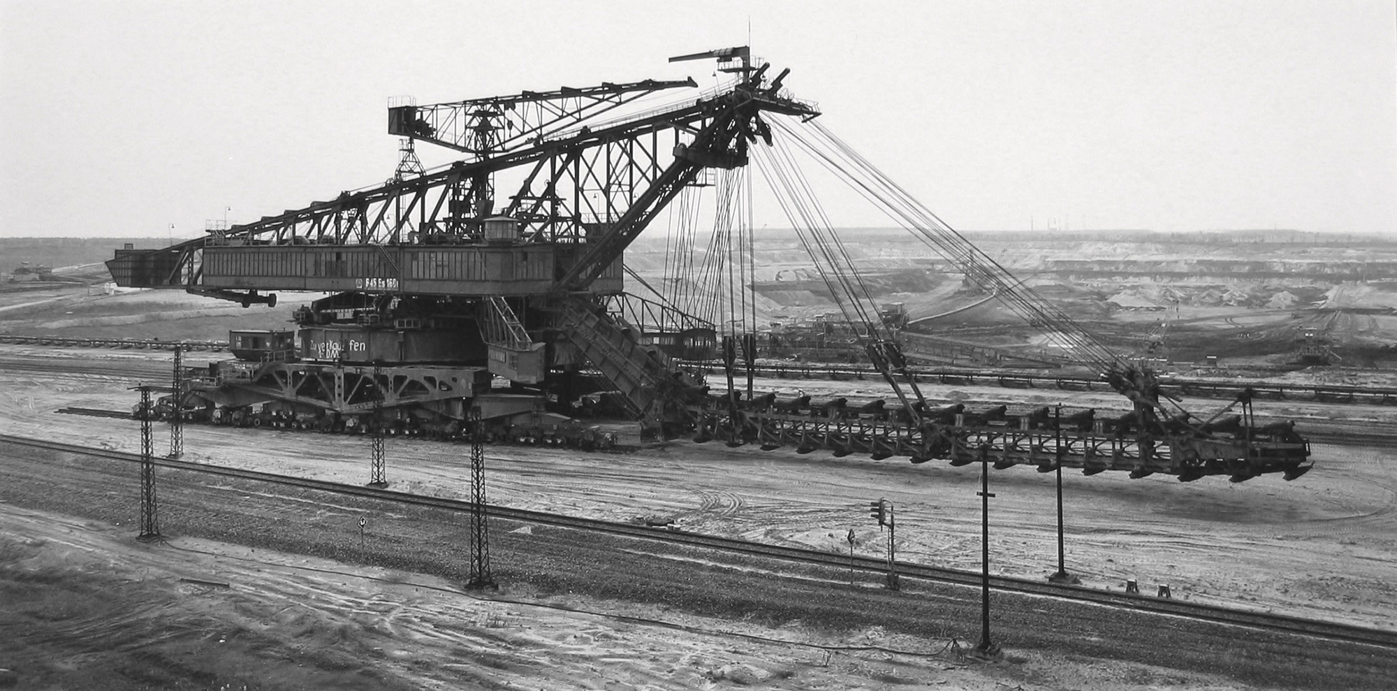 "<span class=""link fancybox-details-link""><a href=""/artists/128-claudia-fahrenkemper/works/35244-claudia-fahrenkemper-bucket-chain-excavator-lignite-mine-grobern-germany-1991/"">View Detail Page</a></span><div class=""artist""><strong>Claudia Fährenkemper</strong></div> b. 1959 <div class=""title""><em>Bucket Chain Excavator, Lignite Mine, Gröbern, Germany</em>, 1991</div> <div class=""signed_and_dated"">From the series ""Mining Machinery""<br /> Signed, titled, dated, and editioned, in pencil, au verso<br /> Printed in 2019</div> <div class=""medium"">Gelatin silver print</div> <div class=""dimensions"">10 ½ x 19 ¾ inch (26.67 x 50.17 cm)</div> <div class=""edition_details"">Edition of 8 + 3 APs (#1/8)</div>"