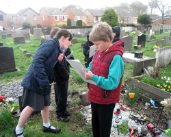 Children writing in a graveyard setting