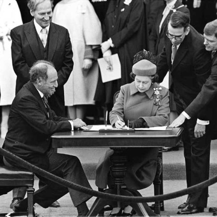 The Queen signs Canada's constitutional proclamation in Ottawa on April 17, 1982 as Prime Minister Pierre Trudeau looks on