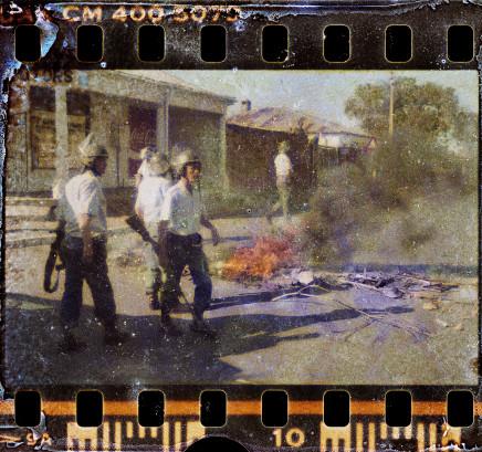 Gideon Mendel, RIOT POLICE DISMANTLE A BURNING BARRICADE..., 1985