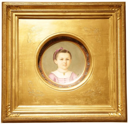 Porcelain plate adorned with a portrait of a child in the center, in a molding frame.