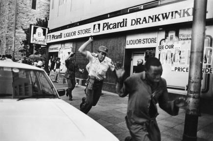 Gideon Mendel, POLICE ATTACK DEMONSTRATORS IN CENTRAL JOHANNESBURG..., 1986