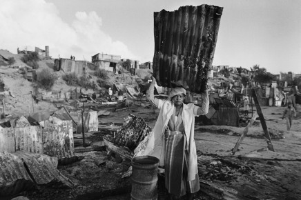 Gideon Mendel, A WOMAN SALVAGES BUILDING MATERIAL AFTER HER SHACK WAS BURNT... , 1986