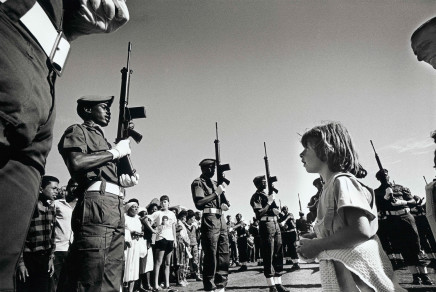 Gideon Mendel, A young white girl watches black soldiers..., 1986