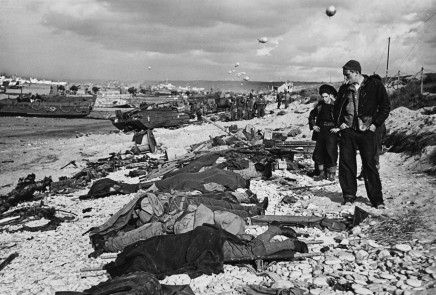 Robert Capa, French fishermen looking at fallen soldiers before funeral on Omaha Beach, June, Normandy, France, 1944
