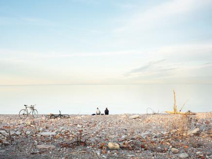 Robert Burley, Cyclists on the shoreline of the Endikement, Tommy Thompson Park, Toronto, 2020