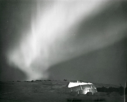 Richard Harrington, Northwest Territories, Northern lights flare over lantern lighted igloo, 1950