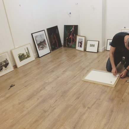 Florian attaching D-rings and string, paintings around the room