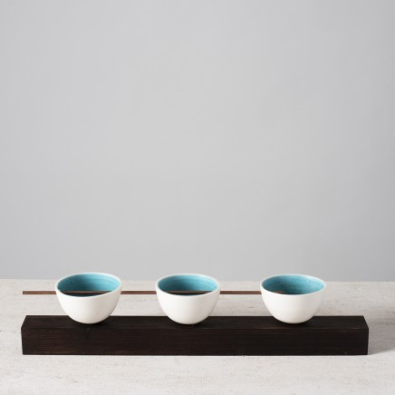 Lynne Rossington Group of Three Thrown Bowls Balanced on Wenge Timber Plinth with Copper Rod Porcelain glazed with turquoise on the inside L: 41cm