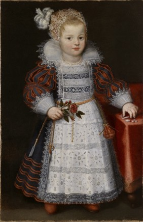 Dutch School, Friesland painter, Portrait of a little girl standing in an interior dressed in a richly embroidered dress with white lawn pinafore and open lace collar; her head-dress is in white lace with a large white feather. She stands by a table with a red tablecloth with some sweet-