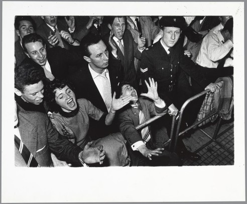 Ed van der Elsken, Visitors of a concert and an agent behind crowd barriers at a concert of the Lionel Hampton Big Band in the Houtrusthallen in The Hague, 24 March, 1956.