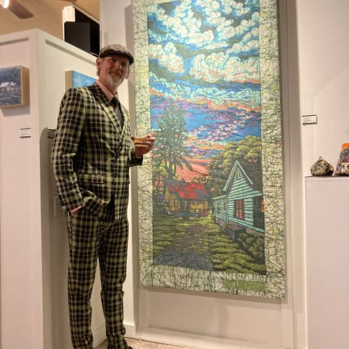 Mulfinger next to one of his batik pieces for an exhibit at Bakova Gallery
