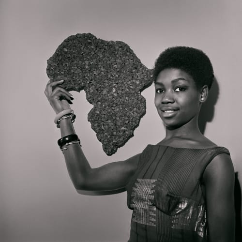 Kwame Brathwaite, Untitled (Nomsa with Africa corckboard at AJASS studios) (1964). Archival pigment print.