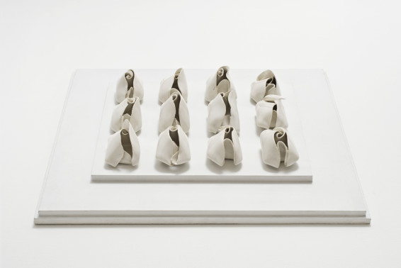 Hannah Wilke Untitled, 1977 Glazed porcelain, painted board (12 gestural fold sculptures) 4.4 x 7 x 4.1 cm, 1 3/4 x 2 3/4 x 1 5/8 ins, each 7 x 44.5 x 39.4 cm, 2 3/4 x 17 1/2 x 15 1/2 ins, board second row (left to right) bottom sculpture signed on base 'Wilke 77' (arrangement referring to HW solo 2018)