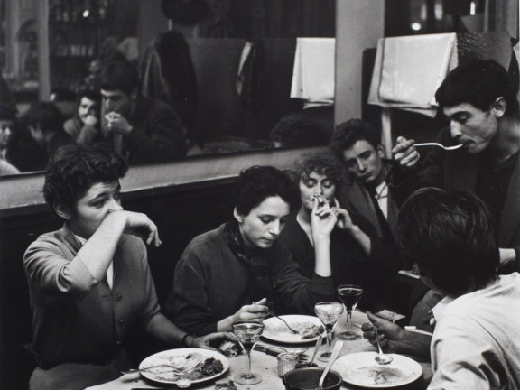 Dinner in a cafe. Girl wipes her nose with her wrist. Paris, ca. 1952