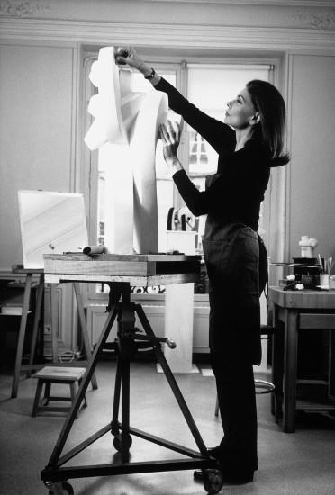 "<span class=""artist""><strong>Sophia Vari</strong></span>, <span class=""title""><em>artist in her studio</em></span>"