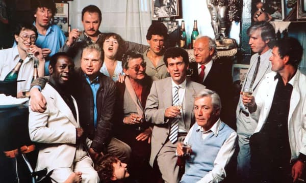 Colony Room Club members in the 1980s, including Michael Wojas (far left), the club's third and final proprietor; Doctor Who actor Tom Baker (standing next to Wojas); the artist Francis Bacon (middle row, second left); and journalist Jeffrey Bernard (seated, front right). Photograph: © Neal Slavin. Courtesy of Darren Coffield
