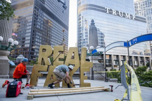 """From left, Terry Karpowicz and Oakley Gregory install a sculpture by Scott Reeder titled """"Real Fake"""" near the intersection of North Wabash Avenue and East Upper Wacker Drive on June 26, 2017, in Chicago. (Armando L. Sanchez / Chicago Tribune)"""