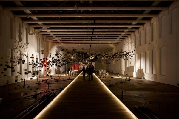 """Glenn Kaino's """"In the Light of a Shadow."""" Sticks and stones and postcards hang from the ceiling or are raised off the floor by thin rods. Theatrical lights cast shadows onto the wall, transforming the objects into birds, drones, sailing ships and meteorites by turn.Credit...Tony Luong"""