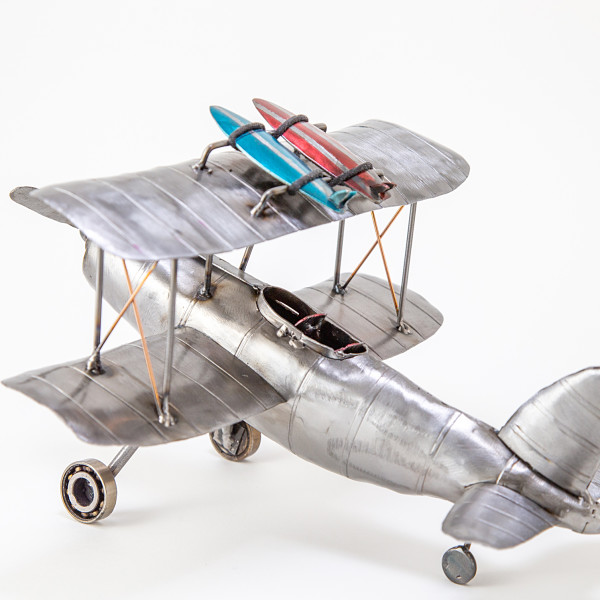 Model biplane sculpture with two surfboards strapped to the top wing, made in lacquered steel with heat applied detail.