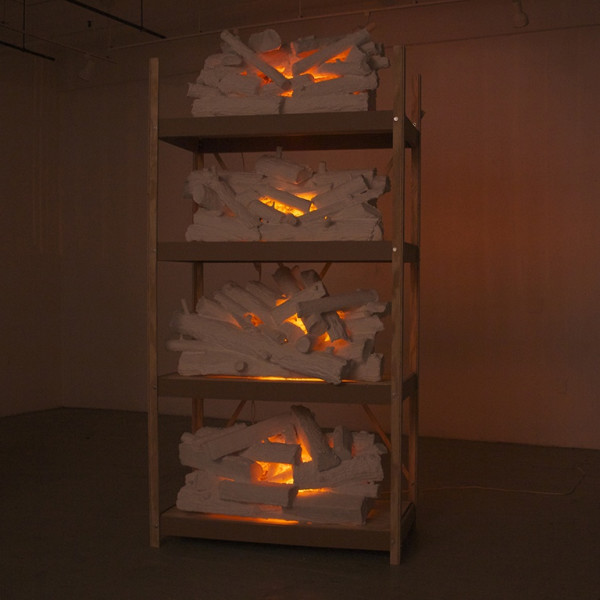 This installation model is four logs that are each lit with fire much like a fire place and each are placed on a bar rack. The colors used are brown, red and orange.