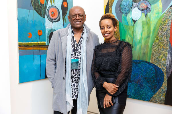 Mesai Haileleul, left, and Rakeb Sile in front of works by Merikokeb Berhanu. Copyright Addis Fine Art