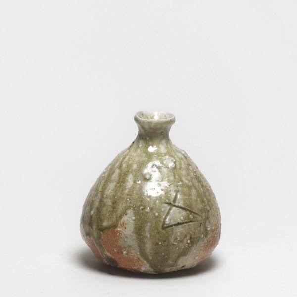 """Shiro Tsujimura #000667 Sakeflasche (tokkuri), 1992 Graubraun gebranntes, helles Steinzeug; glänzendweiße Quarzeinschlüsse; natürliche Aschenglasur (shizenyû); Glasurtropfen am unteren Rand. Signiert: geritztes Zeichen für Ofen (""""kama""""). Holzkasten mit Aufschrift """"Tokkuri""""; signiert: Tsujimura Shirô; Siegel: Shirô 14,1 x 12,5 cm"""