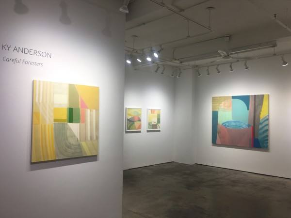 Installation shot of four abstract paintings by Ky Anderson. The painting close by the left is under wall lettering reading,