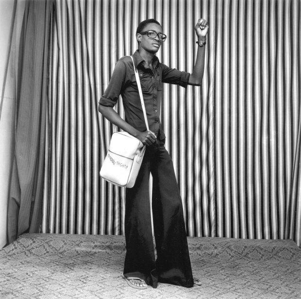 Malick Sidibé, Jeune homme, pattes d'elephant, avec sacoche et montre, 1977, printed later