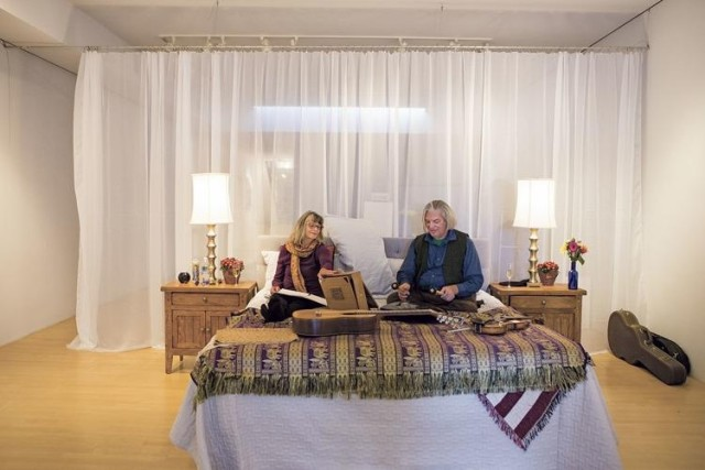 Susan Dollenger and her husband Peter Harrington play music on the bed at Ellsworth Gallery, photo Olivia Harlow/The New Mexican