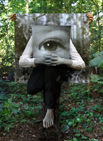 Jonny Briggs, The Hanged Man (self painted grey, cradling photograph of eye as a child, obscuring my own eyes, in front of backdrop held by partner), 2017