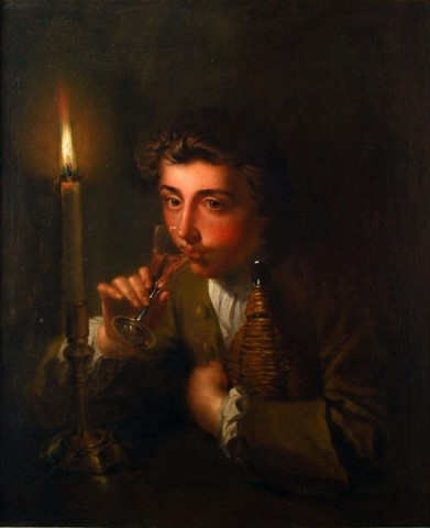 Boy drinking wine by candlelight