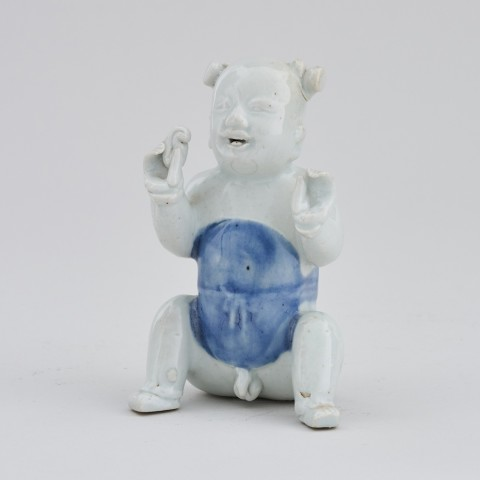 A CHINESE EXPORT MODEL OF A SEATED BOY, first half of the 18th century or earlier