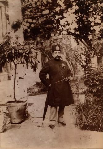 Antoin Sevruguin, Mozaffar ad-Din Shah Qajar in a garden holding a flower, Late 19th Century