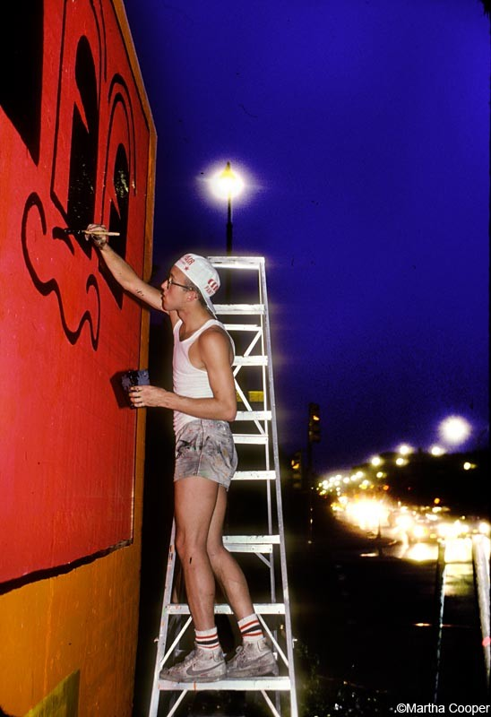 "<span class=""artist""><strong>Martha Cooper</strong></span>, <span class=""title""><em>Keith Haring painting the Bowery Wall (Night)</em></span>"