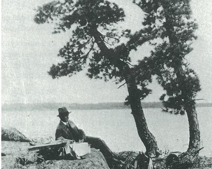 J.E.H. MacDonald sketching under the shade of a poplar tree during his trip to Sturgeon Bay in 1931
