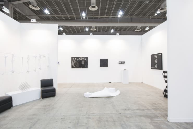 Art fair booth with two abstract steel sculptures, an installation of cut fabric shirts, and three paintings, among other objects. Everything is in shades of black and white.