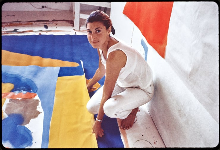 "Helen Frankenthaler in her studio ""in the woods"" in Provincetown, 1968. Working on the floor, she poured thinned paint directly onto raw, unprimed canvas, a technique that established the Color Field movement. Credit: Helen Frankenthaler Foundation, Inc./Artists Rights Society (ARS), New York; J. Paul Getty Trust; via Alexander Liberman Photography Archive; Getty Research Institute"