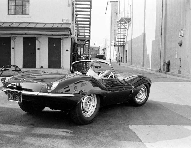 John Dominis - Steve McQueen in black jaguar at studio, CA