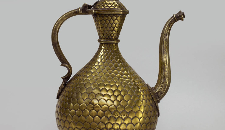 """<div class=""""title""""><em>Brass Ewer with engraved Fish Scale Pattern</em></div><div class=""""year""""> Deccan, early 18th century</div><div class=""""dimensions"""">Height: 32 cm<br></div>"""