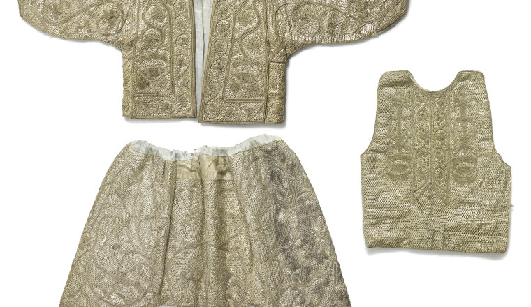 """<div class=""""title""""><em>A boy's circumcision costume consisting of a jacket, short pantaloons and a vest</em></div><div class=""""year""""> Tunisia, Tunis, first half of 20th century</div><div class=""""medium"""">Silver lamella, silver sequins, silver thread, cotton, paper and synthetic satin</div>"""